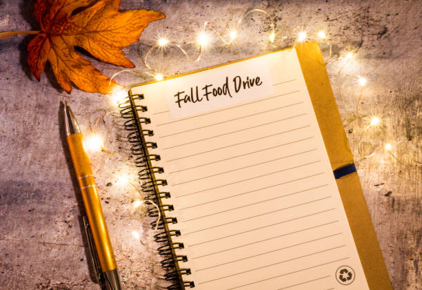 Thanksgiving Food Drive list concept on notebook Thanksgiving Food Drive list concept on notebook surrounded with bright leaves and decorative lights, flat lay food drive stock pictures, royalty-free photos & images