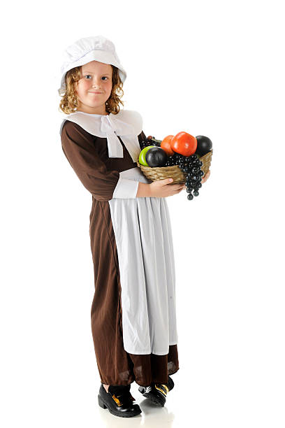 Thanksgiving Fruit-Bearer An elementary Pilgrim girl happily carrying a basket of fruit for the first Thanksgiving feast.  On a white background. pilgrim stock pictures, royalty-free photos & images