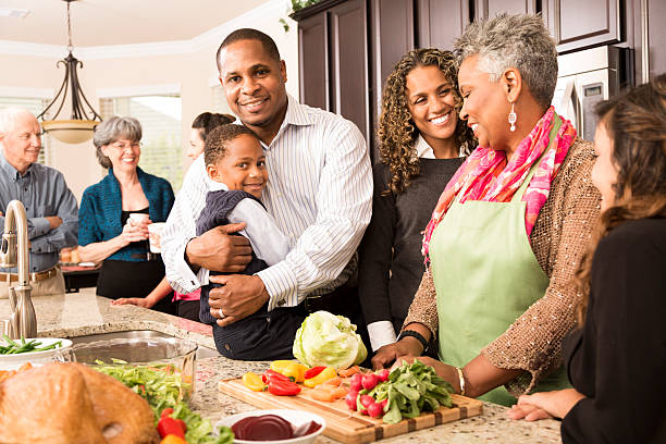 Thanksgiving:  Multi-ethnic family, friends gather in kitchen to prepare meal. stock photo