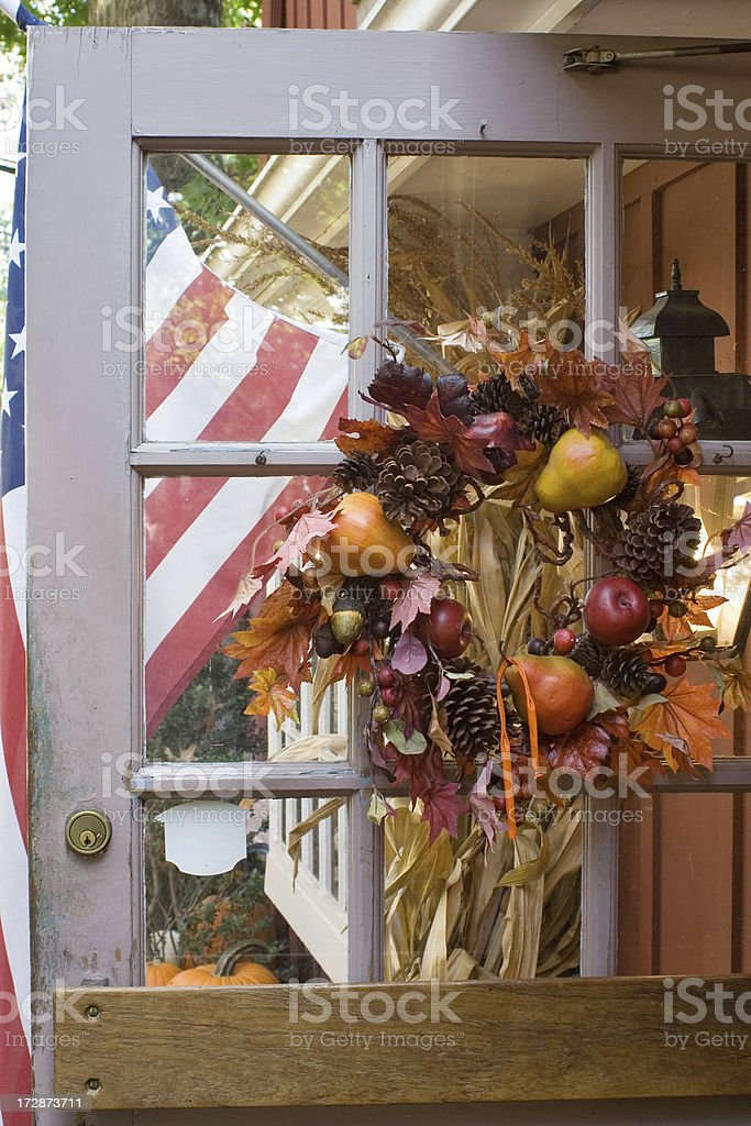 Thanksgiving ornament on the door in front of American flag royalty-free stock photo