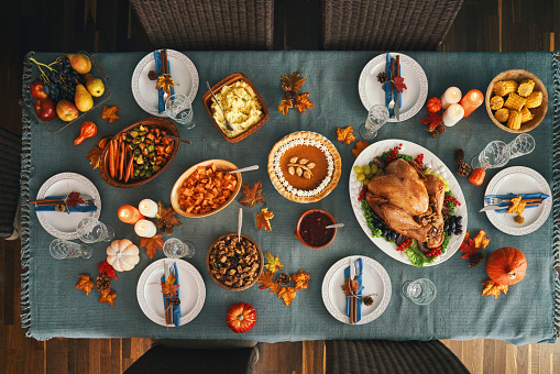 Thanksgiving Party Table Setting. Traditional Holiday Dinner with Stuffed Turkey, Roasted Potatoes, Cranberry Sauce, Vegetables and Pumpkin Pie