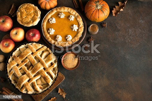 Thanksgiving pumpkin and apple various pies, top view, copy space. Fall traditional homemade apple and pumpkin pie for autumn holiday.