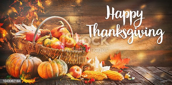 Happy Thanksgiving. Pumpkins with fruits and falling leaves on rustic wooden table