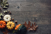 Thanksgiving season still life with colorful small pumpkins, acorn squash and fall leaves over rustic wood background.
