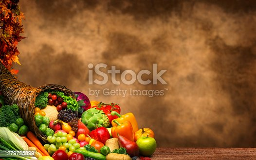 A Thanksgiving still life of a cornucopia full of holiday fruits and vegetables in front of a rustic background that provides ample room for copy and text.