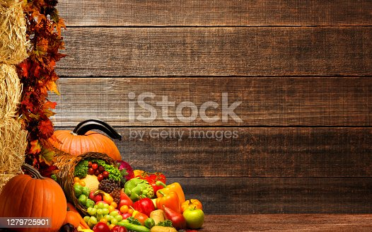A Thanksgiving still life that includes pumpkins, a stack of hay bales; and a cornucopia full of holiday fruits and vegetables in front of a rustic wood wall that provides ample room for copy and text.