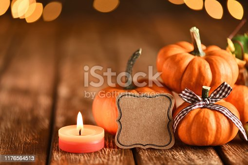 Thanksgiving still life with pumpkins and empty greeting card on illuminated background and a rustic wooden table