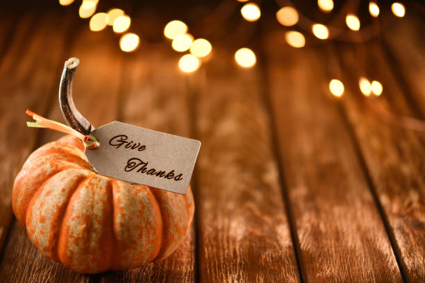 Thanksgiving still life with pumpkins and greeting card on a rustic wooden table stock photo