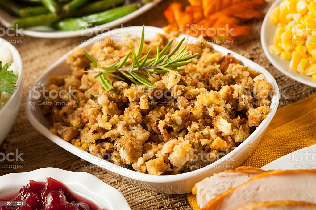 Thanksgiving stuffing amidst other dishes on a table stock photo