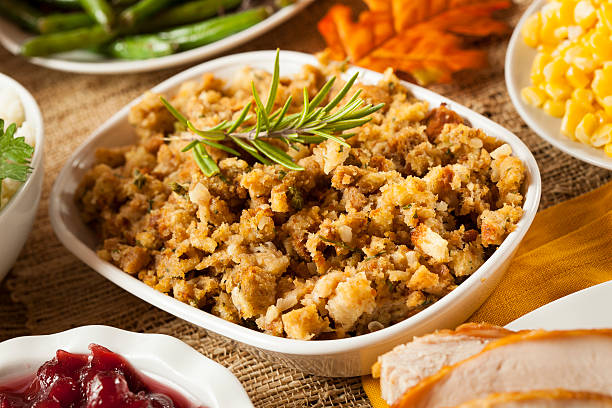 Thanksgiving stuffing amidst other dishes on a table Homemade Thanksgiving Stuffing Made with Bread and Herbs amidst stock pictures, royalty-free photos & images