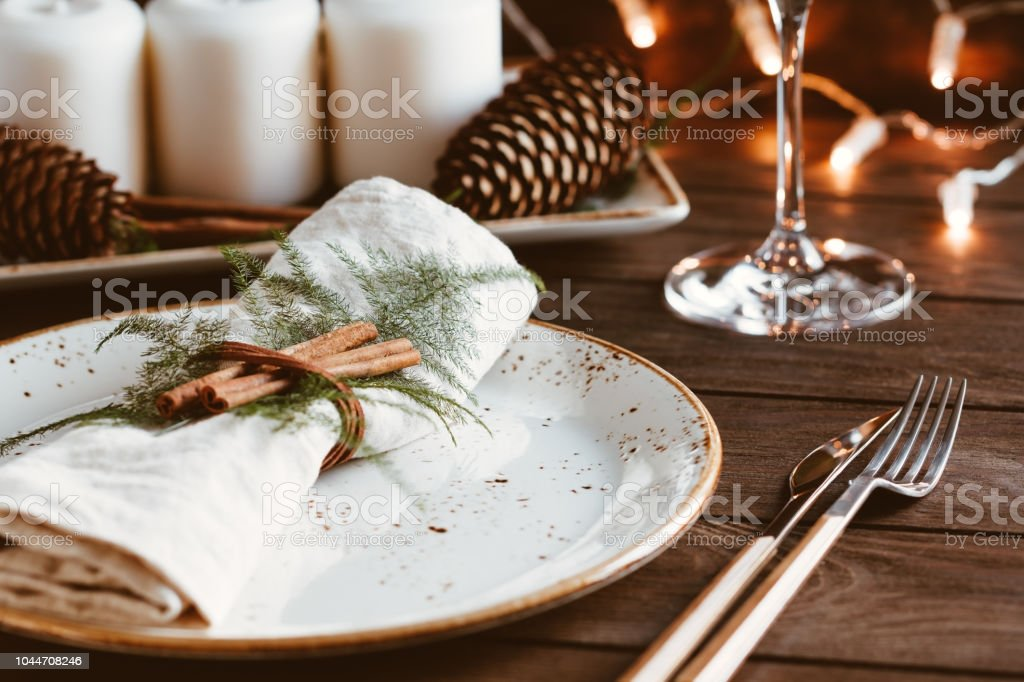 Thanksgiving table setting among white candles and cones. Ceramic plate with fork and knife on a linen napkin. The concept of a festive dinner. - Foto stock royalty-free di Ambientazione