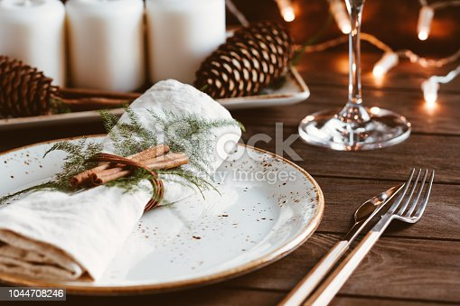Thanksgiving table setting among white candles and cones. Ceramic plate with fork and knife on a linen napkin. The concept of a festive dinner.