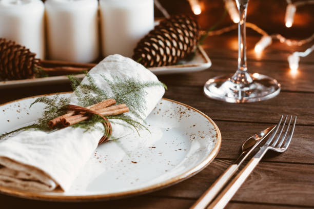 thanksgiving table setting among white candles and cones. ceramic plate with fork and knife on a linen napkin. the concept of a festive dinner. - christmas table foto e immagini stock