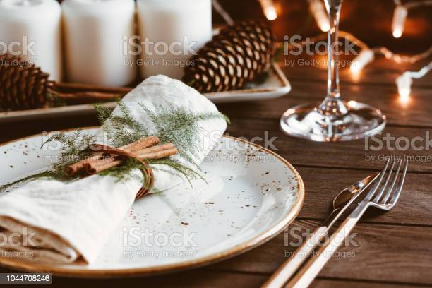 Thanksgiving Table Setting Among White Candles And Cones Ceramic Plate With Fork And Knife On A Linen Napkin The Concept Of A Festive Dinner - Fotografie stock e altre immagini di Ambientazione