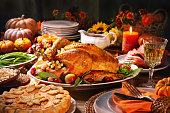 Thanksgiving dinner. Roasted turkey garnished with cranberries on a rustic style table decoraded with pumpkins, vegetables, pie, flowers, and candles