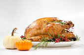 Thanksgiving pepper roasted turkey garnished with blackberry, pink peppercorn, and mini pumpkins on white.\