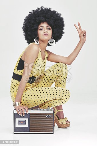 A young woman wearing a 70s retro jumpsuit sitting by a cassette player showing the peace signhttp://195.154.178.81/DATA/i_collage/pi/shoots/782690.jpg