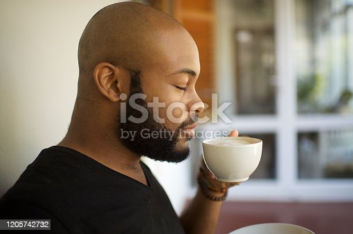 A 20-24-year-old African young male with a shaven bald head and black beard side view portrait enjoying a cup of coffee.  He enjoys the coffee and is smiling.  He is sitting on an outside porch of a restaurant or at home.  He looks happy and relaxed.