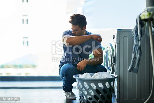 Shot of a young man doing household chores