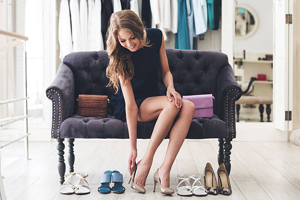 That is perfect pair! Beautiful young woman trying on high heel shoes while sitting on sofa at the shoe store stylish stock pictures, royalty-free photos & images