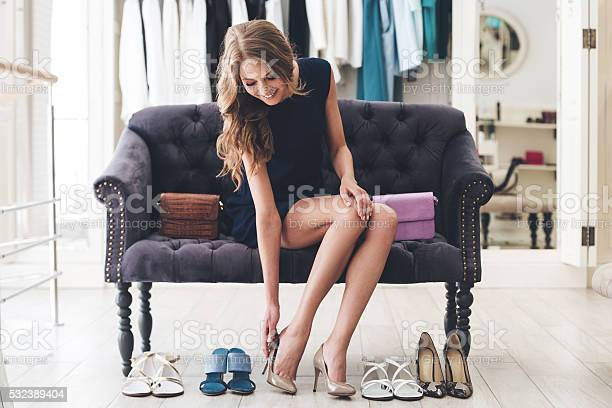 Beautiful young woman trying on high heel shoes while sitting on sofa at the shoe store