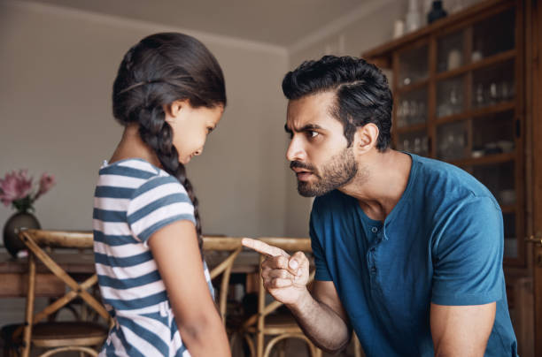 That is very naughty! Shot of a father disciplining his daughter at home scolding stock pictures, royalty-free photos & images
