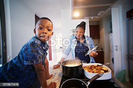 African mother and son busy at in the kitchen with the boy looking at the camera licking his lips while the other smile Strand Cape Town South Africa
