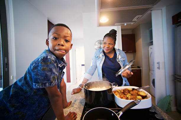 That looks scrumptious; Boy Licking lips African mother and son busy at in the kitchen with the boy looking at the camera licking his lips while the other smile Strand Cape Town South Africa pap smear stock pictures, royalty-free photos & images