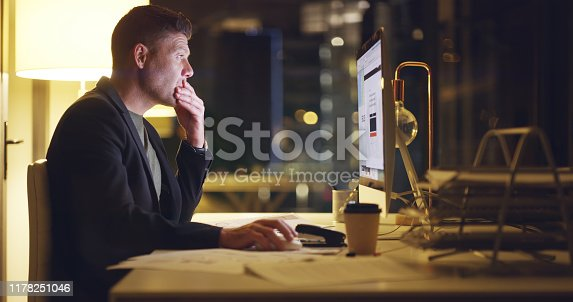 Shot of a mature businessman using a computer during late night at work