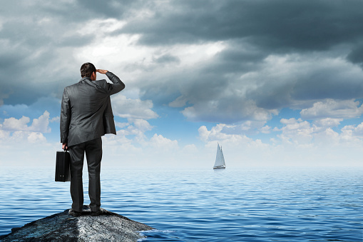 A man dressed in a suit and carrying a briefcase stands on a rock at the shore and looks out into the distance and realizes that his ship has sailed.
