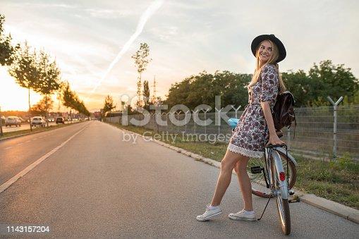Young lady enjoying sunlight on a side walk