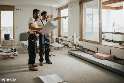 Full length of construction workers analyzing blueprints in the apartment while one of them is aiming at distance.