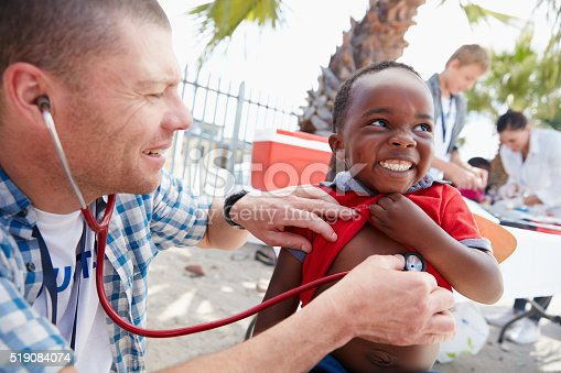 Shot of a volunteer doctor giving checkups to underprivileged kids