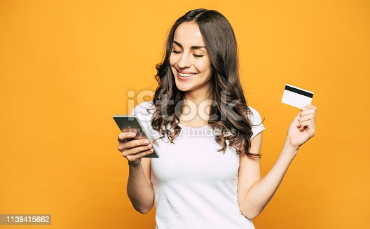 A girl with a credit card in one hand and a mobile phone in other is showing her pleasant emotions and satisfaction because of using this devices.