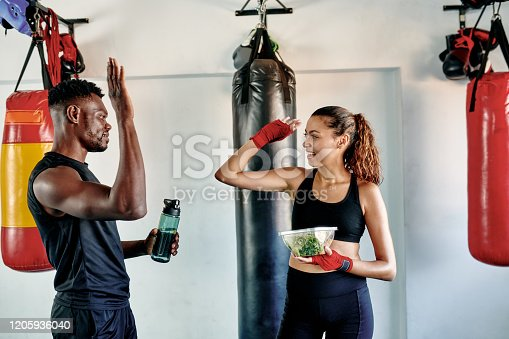 Cropped shot of an attractive young female boxer high fiving her fitness coach during their lunch break in a gym