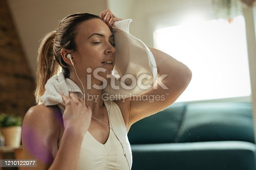 Exhausted athletic woman wiping sweat with a towel after exercising at home.