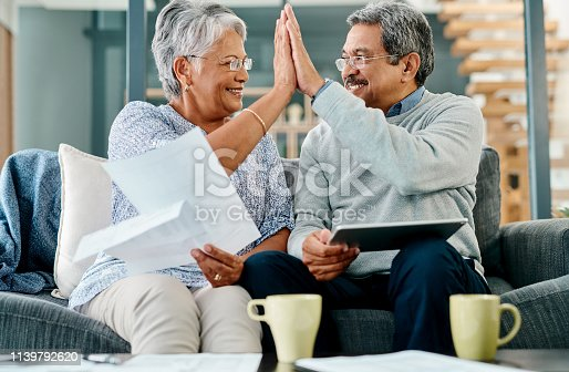 Shot of a mature couple giving each other a high five while sorting their finances together at home