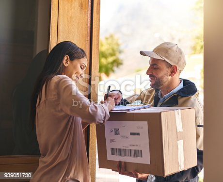 Shot of a young woman signing for her delivery from the courier
