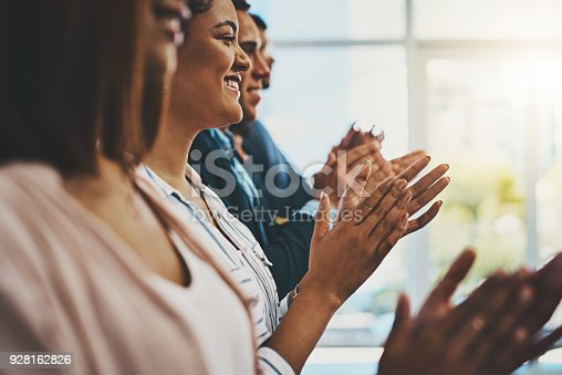 Shot of a group of businesspeople applauding in an office