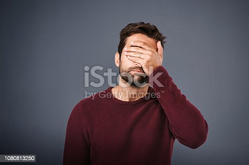 Studio shot of a young man covering his eyes in regret against a gray background