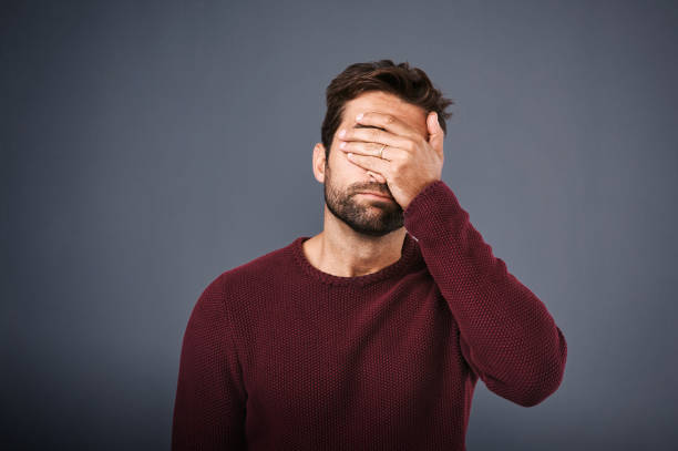 That was such a flop Studio shot of a young man covering his eyes in regret against a gray background guilty stock pictures, royalty-free photos & images