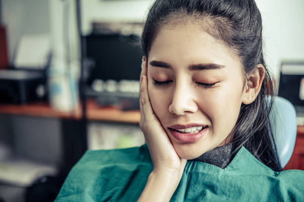 That woman had a toothache and a hand touch her cheek. stock photo