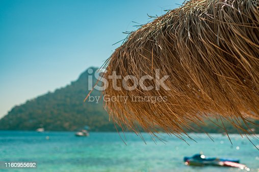 istock Thatched Beach Shade With Tropical Island and Boats on Turquoise Sea in the Background 1160955692