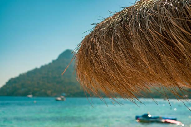 strohstrand schatten mit tropischen insel und boote auf türkis meer im hintergrund - strohdach stock-fotos und bilder
