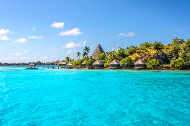 Thatched hut village Bungalows on a reef motu (small island) in the lagoon of Bora Bora Island. French Polynesia, South Pacific Ocean. south pacific ocean stock pictures, royalty-free photos & images