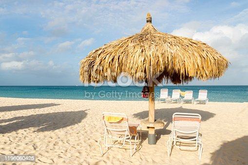 This tranquil beach scene was taken in Aruba.  The beach features white, sugary sand in the foreground and the turquoise Caribbean sea in the background.  A thatched umbrella and lounge chairs sets the idyllic scene.