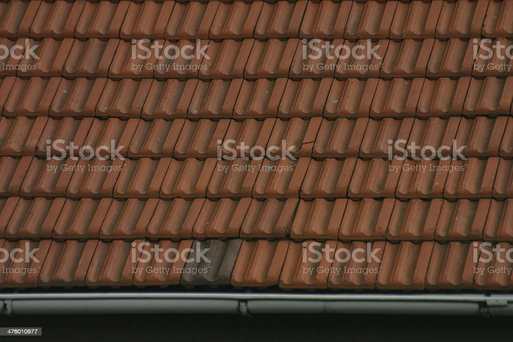 Thatched roof with red tiles stock photo