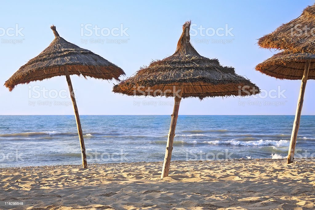 thatched sunshades on the beach stock photo