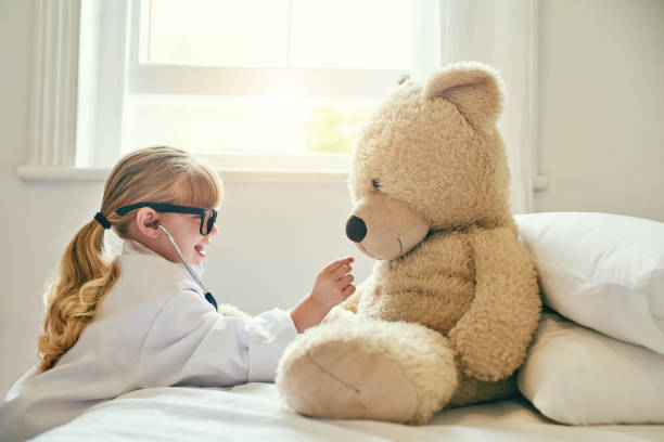 That's a good heart you have there, teddy Shot of an adorable little girl dressed up as a doctor and examining a teddy bear with a stethoscope dressing up stock pictures, royalty-free photos & images