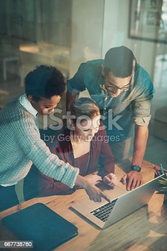 High angle shot of three young businesspeople looking at a laptop